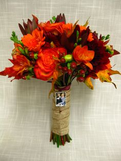 Deep, rich fall toned wedding bouquets perfect for an Autumn wedding in New England. Flowers include circus roses, black bacarra roses, orange freesia, orange gerbera daisies, safari sunset and fall leaves.