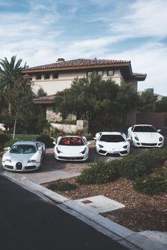 A Bugatti, a Ferrari, a Lamborghini and another Ferrari in front of a House