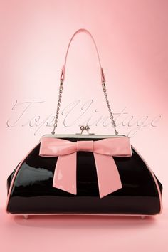 Pretty as a picture by day, perfectly presentable for night, the 50s Bow Handbag in Black and Pinkfrom Pinup Couturehas what it takes to be your favourite arm candy!Madefrom durable shiny black vinyl, edged with shiny pink piping to give this purse subtle curves and a classic shape, trés chique!The inside hasa beautifulblack lining with a silver zipper compartment and open inner pockets that provide space-saving organization within;your wallet...