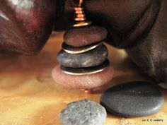 Oregon beach rocks have been gathered, stacked and drilled into a rock cairn pendant. German silver bench scraps are added to the cairn as well. The stones are drilled the way they naturally stack. The stones can be turned on the copper head pin so this pendant could also be used as a contemplative device.