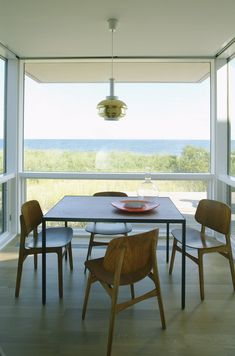 Stelle Architects designed the Dune Road Residence in Bridgehampton, New York.  all glass dining room, open, views, windows floor to ceiling, wall to wall glass
