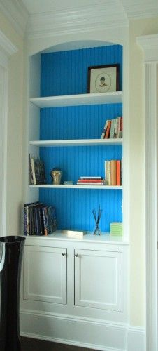 Built ins with beadboard backs to tie in with the walls.  I like it more than fabric or wallpaper backing.