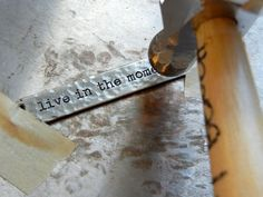 Use the pein side of a chasing hammer and a steel block to add texture to Tim Holtz idea-ology word bands.