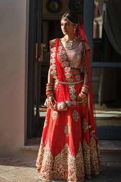 Red and gold wedding Lehenga. Photo by Virginia Gimeno