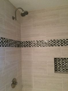 """Beautiful 12x24"""" porcelain tile with a mosaic accent and shampoo cubby. Rain shower head raised for taller adults."""