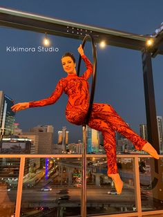 Contortionist on freestanding Lyra (no rigging required) in glamorous red sparkling sequined catsuit at quinceanera on penthouse rooftop venue. Magical and mesmerizing aerialists! Perfect for weddings, quinces, galas and any grand event. Once in a lifetime entertainment experiences for your guests. Kikimora Studio High Fashion Circus. Elegant Interactive Entertainment. Over the top opulence. Aerial, lyri, hoop, lollipop, red, fire theme, performance, birthday, sweet 15, quince, sweet 16…