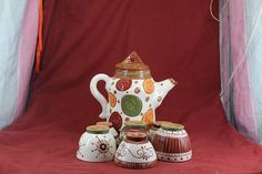 This Tea set, with earthly colours, contains the teapot and six small cups. Each cup is different with its own design making it easy for you to locate your cup when in company with friends.  This object is made of low-temperature clay, the technique Sgraffito and many different dots colors. The object is suitable for food, microwave and dishwasher.  Teapot weight= 1500 gram height= 21,5cm  Glasses weight= 100 gram height= 6cm