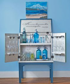 The special paints featured in the Country Living Artisans Collection from Caromal Colours are water-soluble and easy to use. Since they can be applied on almost any surface, Larry was even able to silver-leaf the metal rails that keep wineglasses secure on doors. A toner applied to the silver leaf adds depth and makes barware sparkle. Vintage seltzer bottles, colorful glasses, and silver accessories support the cabinet's distinctive palette.