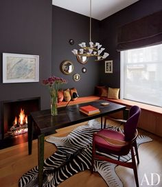 The office of a New York townhouse renovated by D'Apostrophe Design and Selldorf Architects showcases a Gino Sarfatti light fixture, Jean Prouvé desk, and Finn Juhl chair; the mirrors are by Line Vautrin, the artworks are by Cy Twombly (left) and Jean Dubuffet, and the banquette cushions are clad in a Great Plains fabric. Photo: Oberto Gili