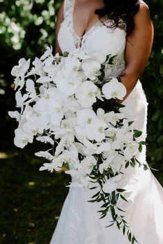 Janelle's wedding bouquet contained gorgeous white orchids and greenery. Like what you see? Find more summer wedding ideas from the full wedding album on The Knot. Personalize your wedding and put a spin on tradition with The Knot's customizable wedding websites, wedding invitations, registry (and more!). Not sure where to start? Get ideas and advice from our editors on everything from wedding colors and venue types to all things guest.