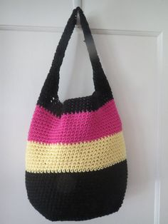 Colorful and stylish hand crocheted bag in black, pink and yellow all cotton yarns. Perfect hand bag, tote or shopper. Contemporary, boho or hippie chic. Fun light weight summer bag measures 12 1/2 inches tall by 13 inches wide with a base of 41/2 inches by 7 inches and handle of 19 inches. You wont believe how much this holds. This bag can be lined in coordinating fabric for an additional fee; use custom order feature.