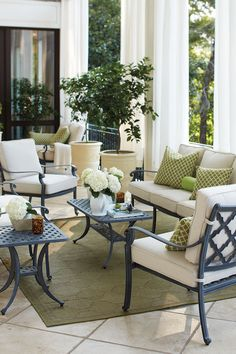 Create two distinct seating areas on a porch that's longer than it is deep -- here we've got a seating area with a loveseat and two chairs. Then in the background, you can see a pair of chairs.
