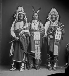 Portrait (Front) of Three Men, Eugene Brunot, White Swan And Edward Hoski: All in Partial Native Dress, Two with Peace Medals, Two with Headdresses, All with Breastplates, All Holding Bags, One Holding Pipe-Tomahawk, One Holding Pipe 24 MAR 1904