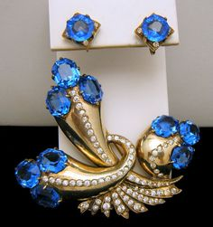 Stunning Sapphire Blue Rhinestone Eisenberg Sterling Fur Clip and Earring Set. The Clip is marked Eisenberg and Sterling. The Earrings are only marked Sterling on the Screw Backs...and logically, there is no place on the setting for additional marks.  The Fur Clip Measures 3 Long and 3 1/4 Wide. Earrings are Screw Backed and Measure 5/8 Square Approximately. Condition is Excellent with No Flaws with Some Patina.