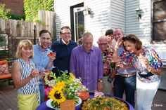 Guests gather to celebrate the fresh summer meal at a backyard garden party. Sunflowers are the perfect reflection of their excitement!