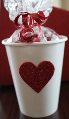 Inexpensive DIY Valentine Favor Idea  Dollar Store Cup (white/red/pink), heart shaped sticker, clear cellophane bag filled with candy and ribbon....