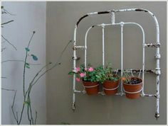 Repurposed iron bed makes beautiful wall art with plants.