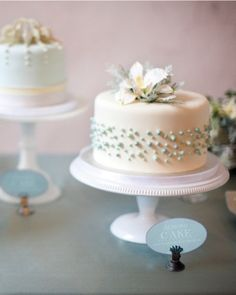 Almond, coconut, and banana-nut cakes iced with pastel fondant and topped with sugar flowers