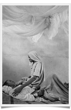 Una mujer cuida de su enfermo hijo en el hospital del campo de desplazados de Mornei, Darfur, Sudan. Imagen de 2004.