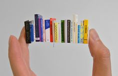 Henrik Franklin produces a table of tiny books for miniature art gallery