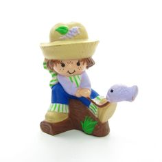 """This vintage Strawberryland Miniatures figurine is """"Huckleberry Pie Catching a Fish."""" Huckleberry Pie is a friend of Strawberry Shortcake and is sitting on a log with a fish on the end of his fishing"""