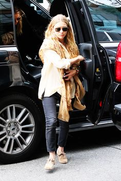 Mary-Kate Olsen wears a beige button-down blouse, scarf, black skinny jeans, and suede shoes