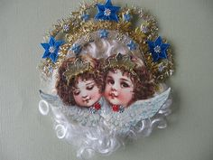 This is a German Scrap of two adorable angel faces. They have been enhanced with glitter, mica, gold dresden and gold roping tinsel crowns .