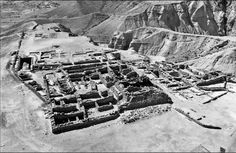 """Qumran Cemetery Information - """"Photograph of the Qumran complex looking south. Graveyard is to the left (east). We can see how the complex was built on a bluff overlooking the Dead Sea. Seven of eleven caves containing scrolls were located in the surrounding cliff faces."""""""
