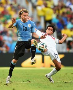 Diego Forlan of Uruguay and Yeltsin Tejeda of Costa Rica battle for the ball during the 2014 FIFA World Cup Brazil Group D match between Uru...