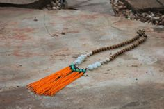 long orange tassel with teal and wood beads