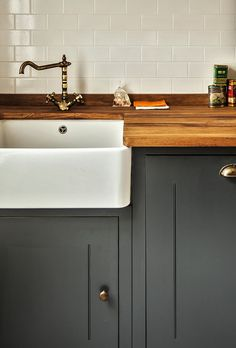 Beautiful industrial kitchen with a classic touch, featuring olive gray cabinets, metal hardware, a white farmhouse sink and oak countertops in front of a white subway tile backplash | Compass & Rose