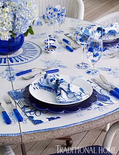 A custom ceramic table made in Italy is set with Pottery Barn stemware, Royal Copenhagen plates, and Tiffany chargers. - Photo: Tria Giovan