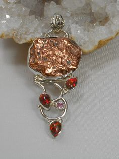 Artisan Native Copper and gemstone pendant with an organic free-form copper nugget center stone, accented with 3 teardrop-shaped cabachon Australian Fire Opal gemstones and 1 faceted Kunzite accent st