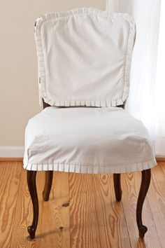 To freshen the look of worn upholstery, separate white slipcovers were made for the chair back and seat. Tiny pleats encircle each piece.