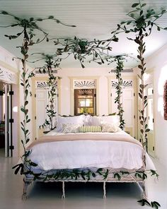In **Celerie Kemble'**s Dominican Republic bedroom, a locally forged iron canopy bed takes center stage and complements the surrounding jungle. The doors and windows are crowned with latticework, and soothing pale green Bellino and D. Porthault linens are additional spots of sunshine.