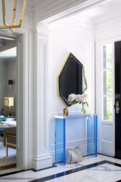 "An asymmetrical brass mirror and transparent blue Lucite console make a modern statement against the entryway's classic black-and-white marble floors. ""Each room is very different, yet the spaces transition so beautifully from one to the next,"" Hepfer says."
