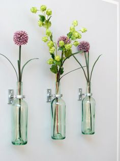 Silk Flowers in Glass Bottles Hung on Curtain rod (?) holders