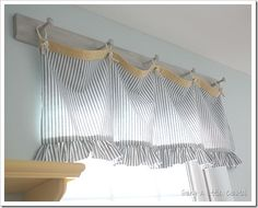 Make valance from some ticking, grommets and a bit of rope for the rings with a piece of wood with pegs for hanging.