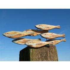Wooden School of Fish Wall Art. Great piece of coastal wall art consisting of distressed wooden fish grouped together on a metal frame to hang on the wall. This stylish piece of wall art would add real seaside charm to any room.