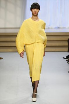 Bright sun yellow silk dress with a oversized bodice with butterfly sleeves and a column skirt to mid calf paired with black nylon stockings and beige Mary Jane sandals. By Jil Sander, from the spring of 2017 Ready-to-Wear Collection
