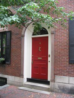 Red door.  Brick house.  Black shutters.