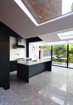 The zigzagging surfaces of the ceiling and walls give the impression that the structure buckled when attached to the existing brickwork.