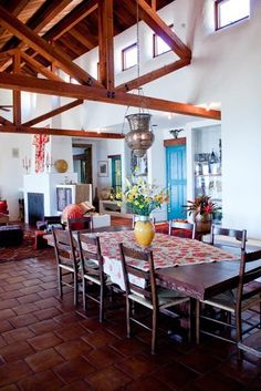 Love this space! From the high beamed ceiling to the blue door and the moroccan lamp over the table.