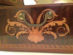 Dettaglio di una maniglia di un cassetto con decori ad intarsi in legno