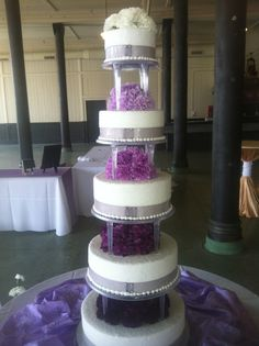 5 tier pillared purple ombre cake with fresh carnations and  silver grey ribbon.