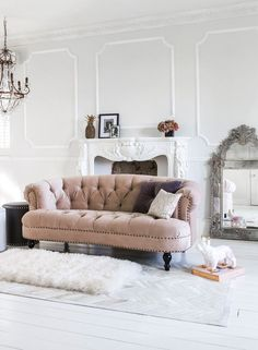 The French Bedroom Company Interiors Blog | Cosy Pink for Autumn in your home. Get ideas for blush pink home accessories, walls and velvet sofa. Top tips on pink and gold, pink and dark blue and sheepskins. Pink velvet chesterfield sofa, Chablis and Roses in vintage shabby chic lounge, with white wooden floor and white fireplace with grey walls. French mirror leaning on wall.