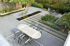 Moderne achtertuin met strakke vijver, vaste bank, bordesroosters en hardhouten schutting met ledverlichting