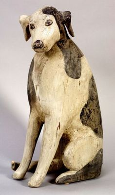 Carved and Painted Pine Folk Art Dog Figure, America, probably early 20th century, seated figure with inquisitive look, applied carved ears and tail, painted white with black spots, (imperfections), ht. 19 1/4, wd. 6 5/8, lg. 12 3/4 in