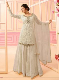 Bollywood diva drashti dhami style off white designer palazzo suit online which is crafted from net fabric with exclusive embroidery and hand work. This stunning designer palazzo suit comes with chanderi jacquard bottom santoon inner and net dupatta. Indian Fashion Dresses, Indian Designer Outfits, Abaya Fashion, Designer Gowns, Pakistani Dresses, Indian Outfits, Pakistani Sharara, Fashion Pants, Eid Dresses