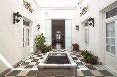 Un patio pompeyano con piso de damero y doble altura emplazado en un PH en el corazón de Recoleta.